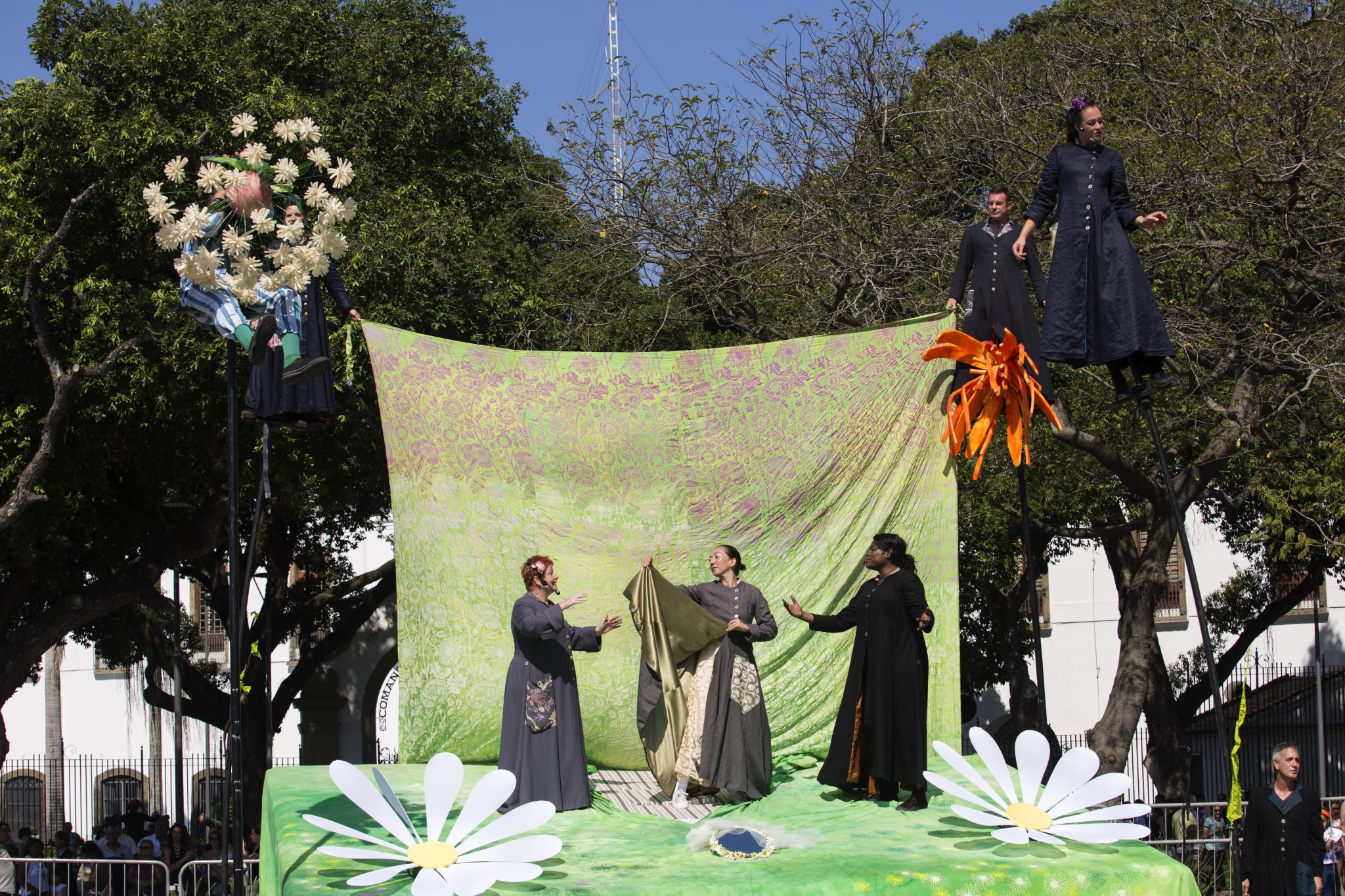 Five performers in The Garden. They are all wearing long blue or grey dresses. Three of them are standing on the stage, in front of a fabric green backdrop. The stage includes two large white flowers. Two perfomers are standing on stills, as if they were standing in the tree to the right of the stage.