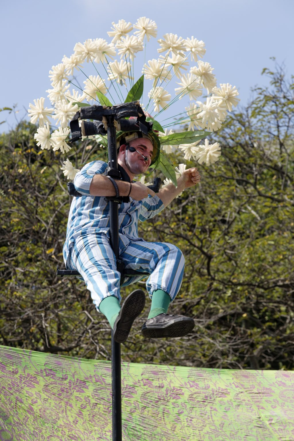Aerial performer in Graeae's The Garden in the Olympic Boulevard in Rio de Janeiro. Large white flowers are attached to his helmet. He is wearing a stripped blue outfit. Trees can be seend out of focus in the background.