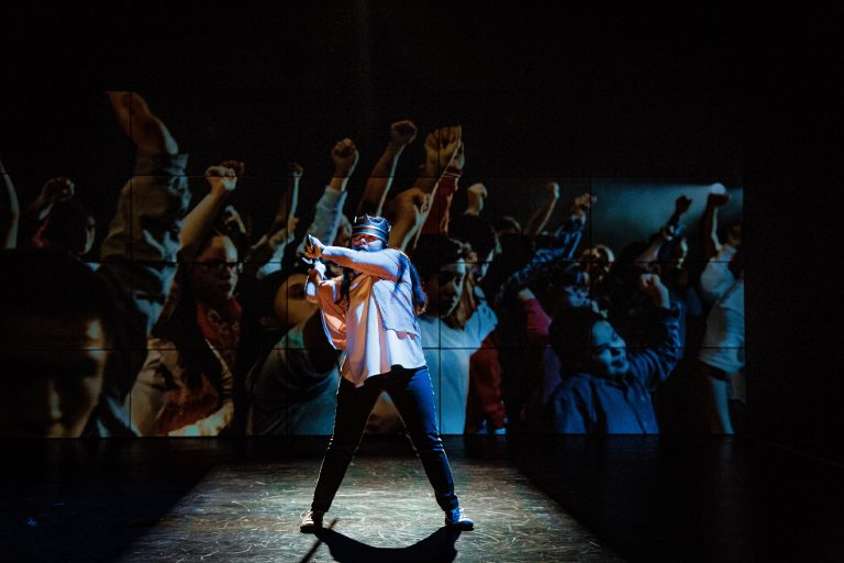 A still image from Hamlet. A performer stands with their feet apart, swinging some kind of weapon. In the background, a large screen is showing images of a crowd, fists in the air, cheering.