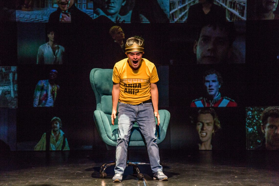 A still image from Hamlet. A performer stands on a stage in front of a teal armchair wearing a yellow t-shirt and blue jeans, with a heavy looking crown perched atop their head. They are facing the audience with their mouth open, as if caught in the middle of a passionate yell. Behind them is a large screen filled with multiple depictions of Shakespearian actors from movies and theatre.