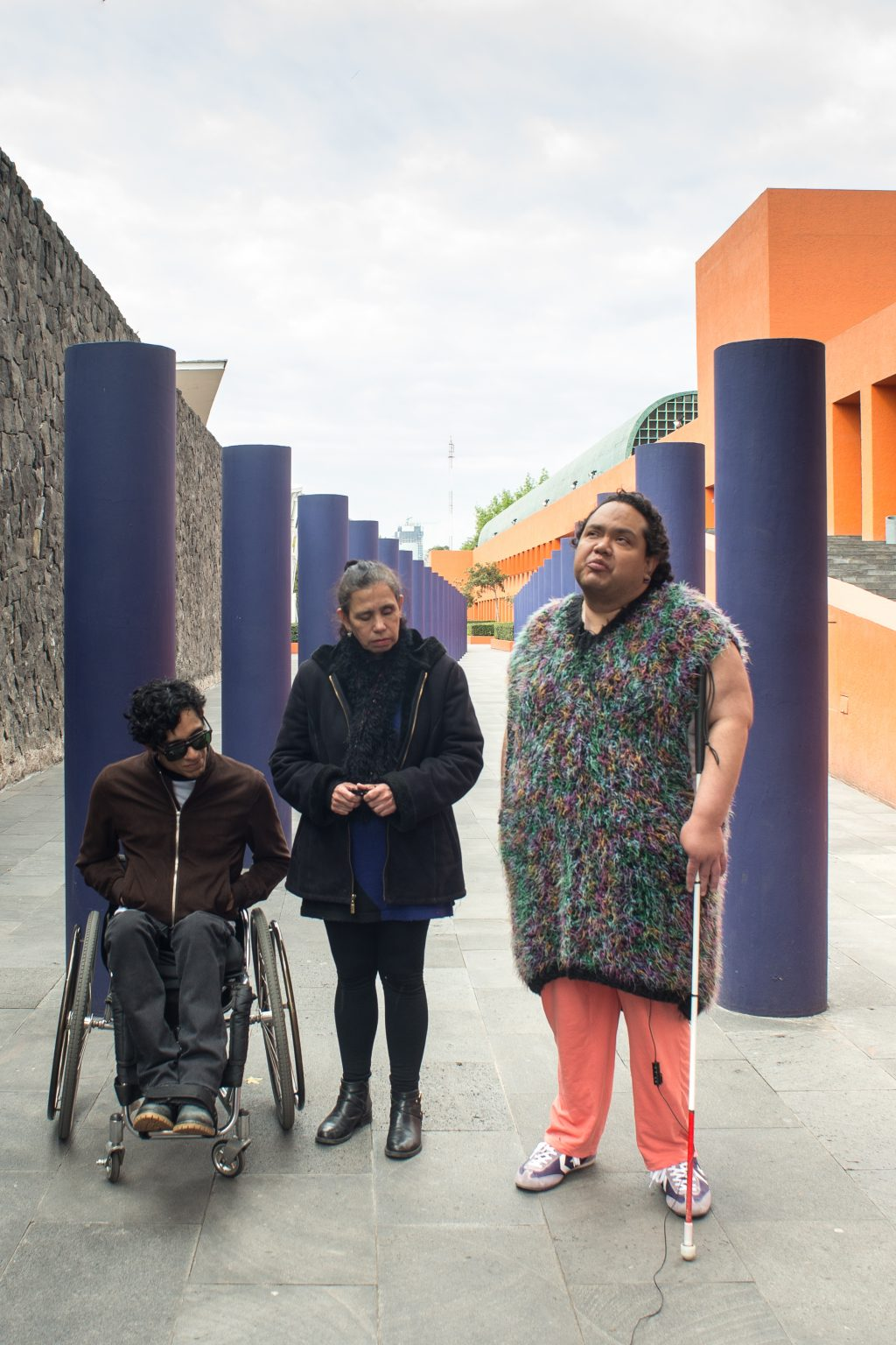 Photo of Edgar Lacolz, Maricarmen Graue, and Pedro Miranda at CENART looking pensive between several cylindrical blue pillars. Edgar is seated in a wheelchair, Maricarmen is standing with no mobility device, and Pedro is on the right holding a white cane.