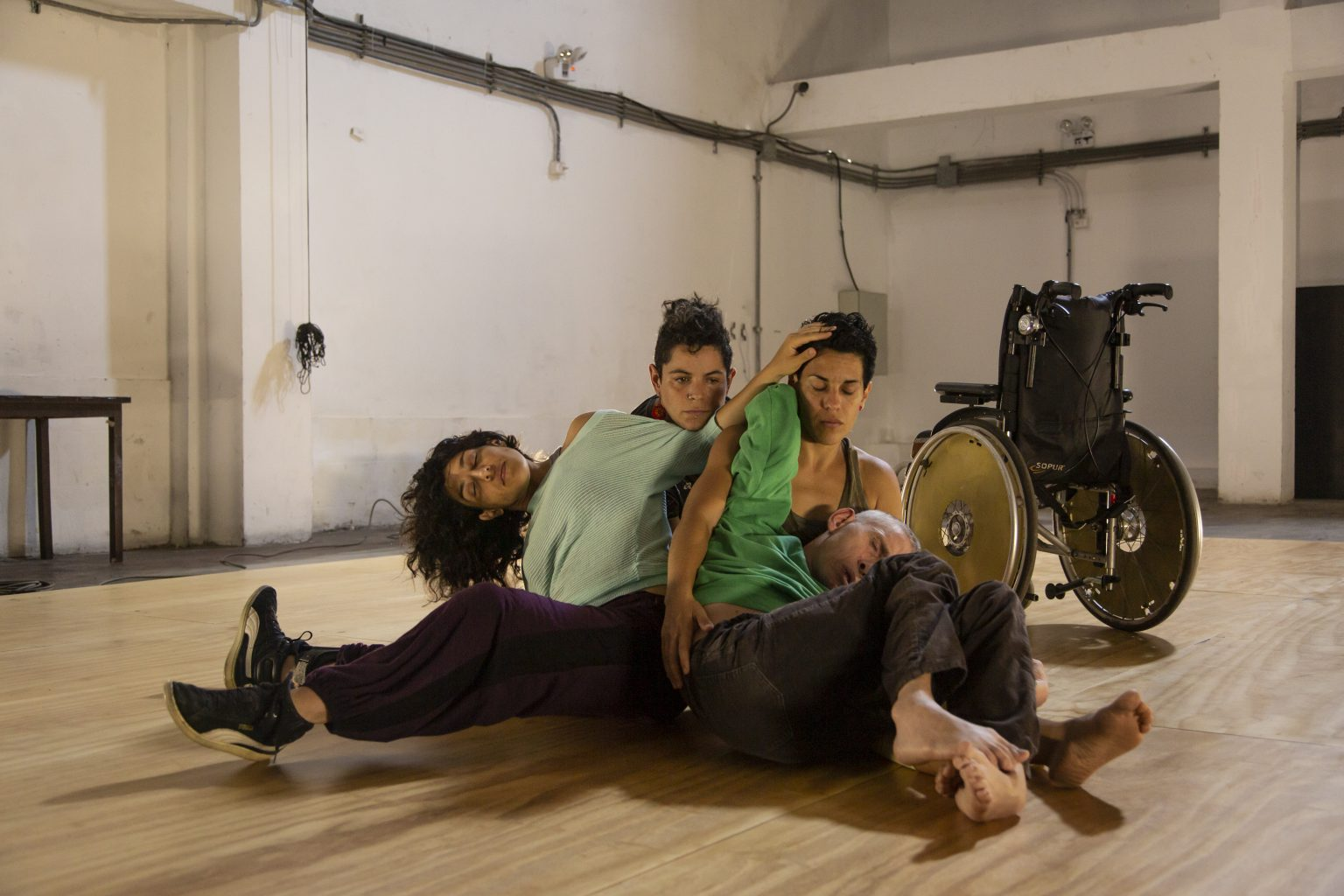 A photo of four dancers seated in a huddle on the floor of a bare studio with a wooden floor. They rest their heads and arms on each other, with eyes closed and bodies entwined. A wheelchair sits empty behind them.