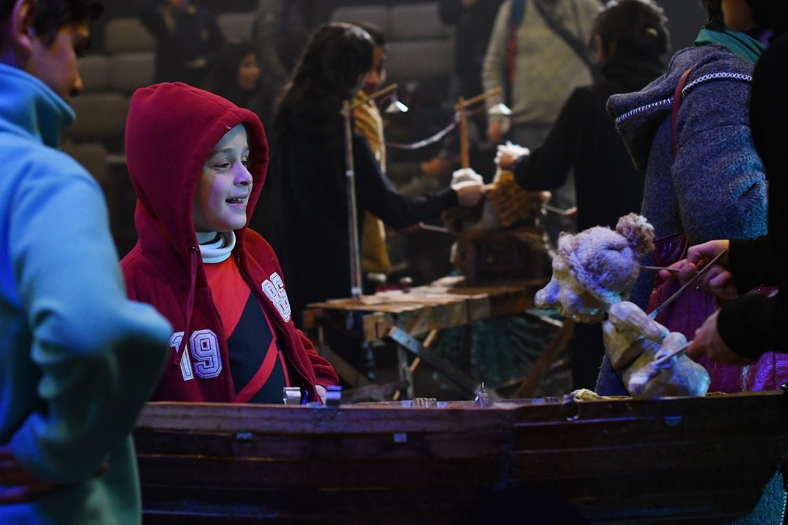 A child in a red hoodie smiles at a puppet on the right side of the image. The puppet is facing the child and wearing a small pink knitted hat. The hands of the puppeteer are just visible behind the puppet, disappearing out of the right side of the image.