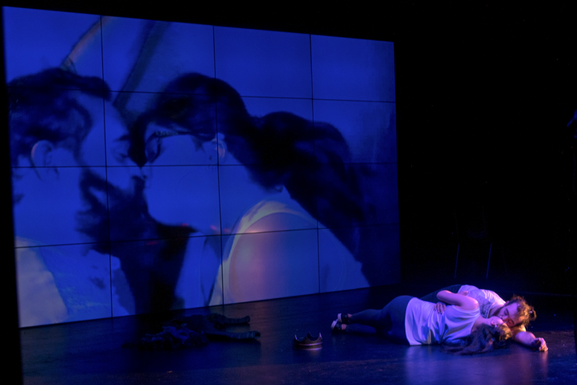 A still image from Hamlet. Two performers lay tenderly facing each other in the middle of a blue-and-purple lit black stage. They are both wearing white t-shirts and dark pants, with each performer resting one hand intimately on the other's waist. At the back of the stage is a large screen showing a close up of the performers from above. Their eyes are closed with their noses pressed together and their lips about to touch.