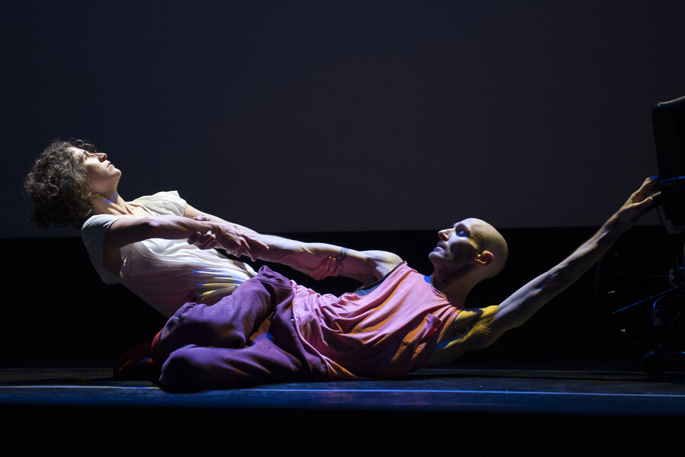 Image from the presentation of creative residency for MayBe - On a stage with a white backdrop, dancer Marc Brew is laying on the ground. His arm is pulled by Giselle Calazans. He is looking at her. His is wearing a pink t-shit and purple pants. She is wearing a white top.