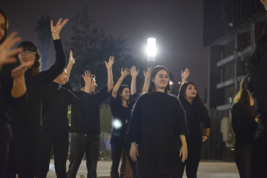 A crowd of people stand outside a tall building at night. They are dressed entirely in black, and are grinning and shaking their open hands over their heads. One woman with lowered arms stands in front of the others, backlit slightly from a distant lamppost.