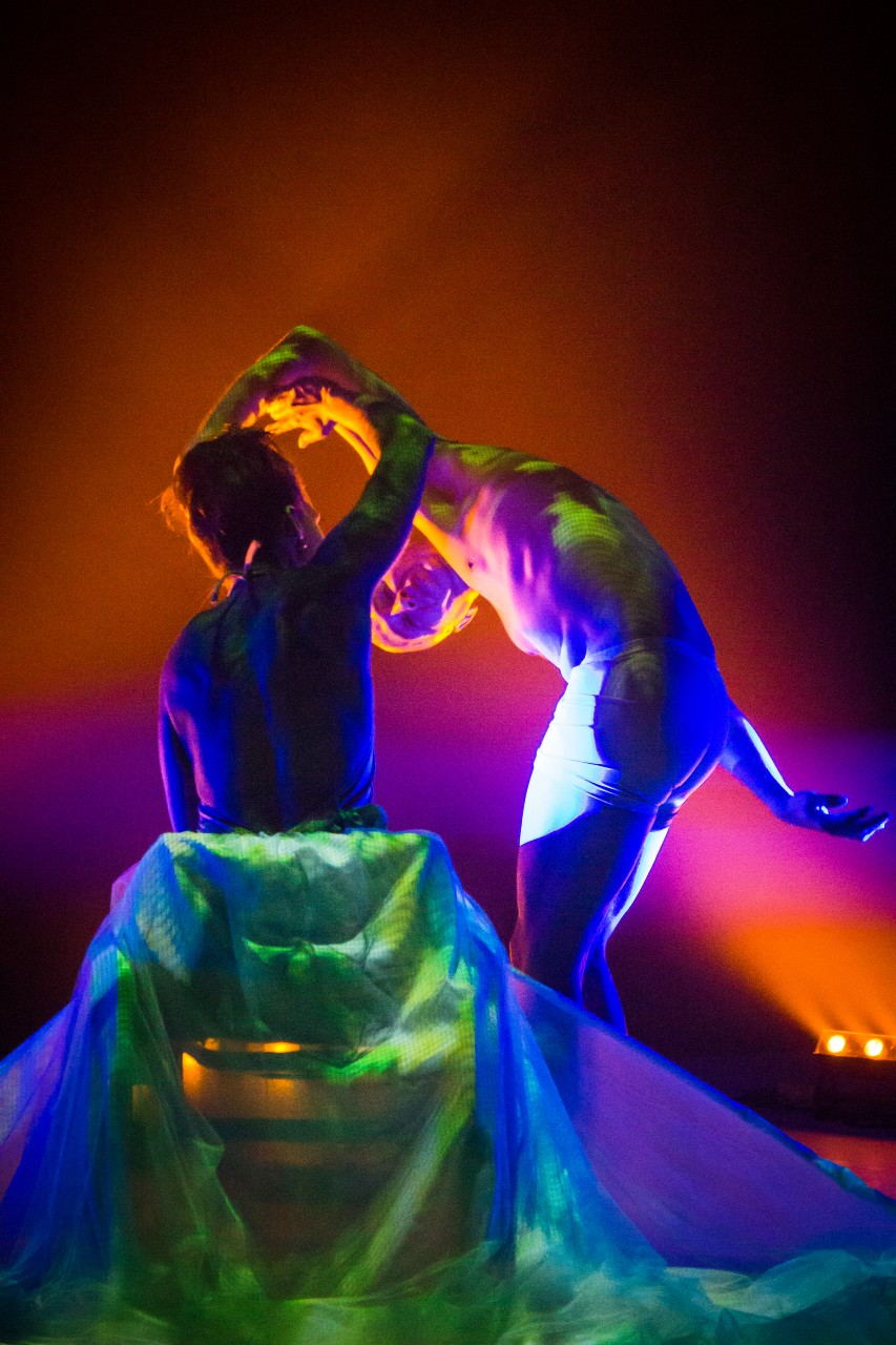 Image of two dancers on stage. Dancer Fabiola Zérega is sitting on a chair, their arm raised above their head, touching the second dancer. The chair is draped with fabric covering the bottom section of the image. The second dancer is standing up bent over looking towards the camera. In the background a colour cast of orange, yellow, purple, and blue light is reflecting on the dancers and the fabric.