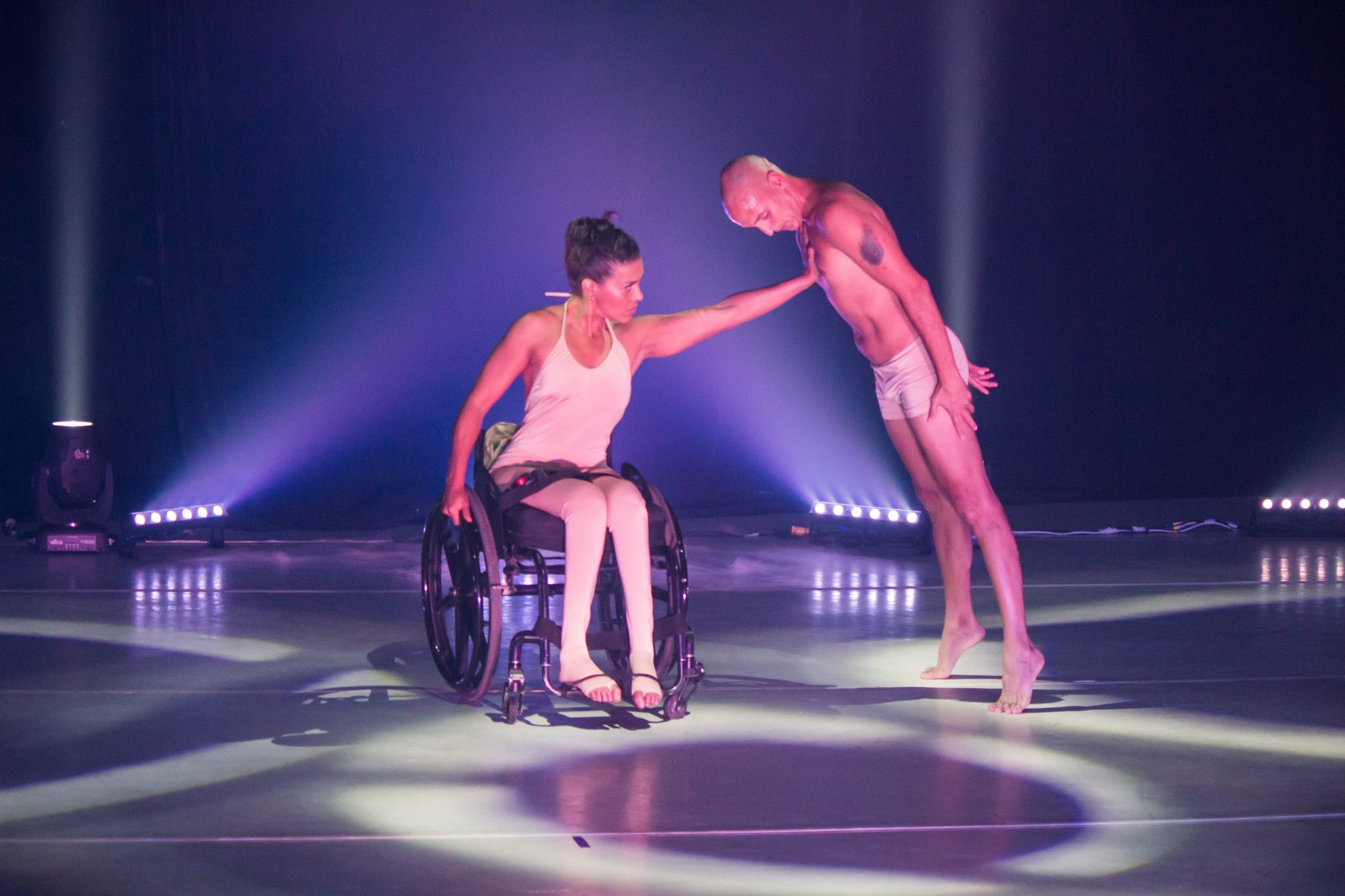 Image of two dancers on a stage cast in pink and blue light. Dancer Fabiola Zérega is sitting in a wheelchair wearing a white/pink full-body leotard. She has one arm on the wheel of her chair, the other is extended, pressing against the chest of the other dancer, looking at her hand. The second dancer is bald, wearing white/pink shorts. They are standing on their toes, looking down and leaning forward supported by Fabiola's hand on their chest.