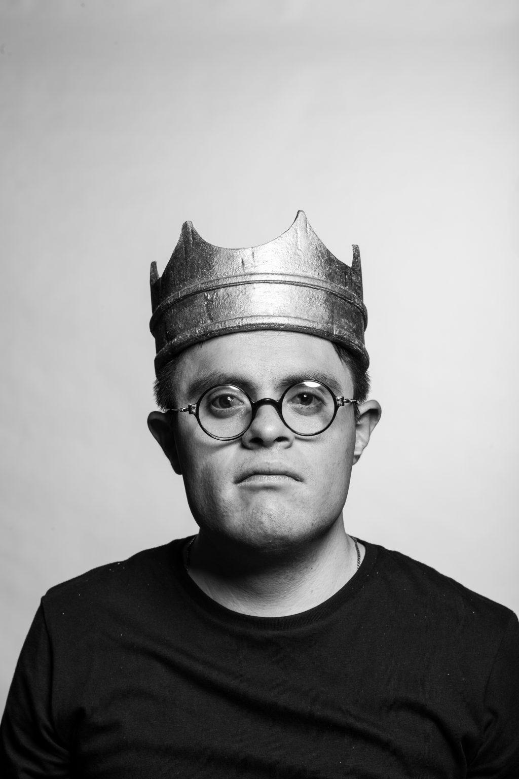 A black and white portrait of an actor in Teatro La Plaza's Hamlet. He is wearing round glasses with a crown on his head and is looking straight at the camera with a serious and deep look on his face.