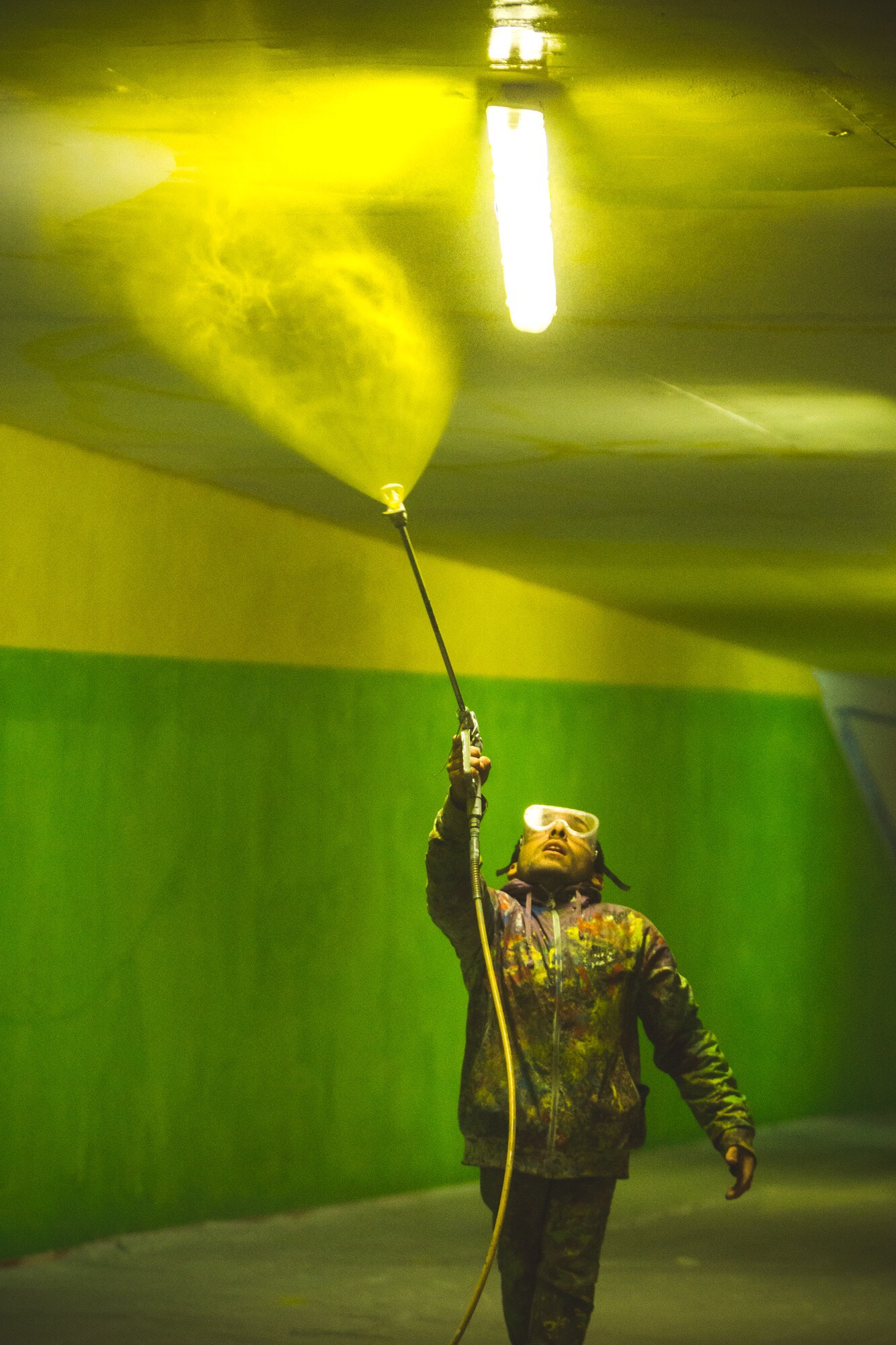 A photo of Elian Chali wearing goggles and looking up at the ceiling above him, which he is spraying with a power washer. The image is lit in a green fluorescent light.
