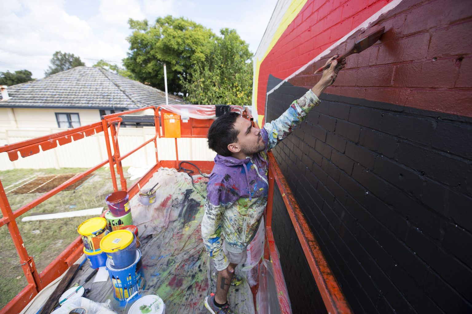 Wide angle profile shot of artist Elian Chali standing on scaffolding painting a mural in brown, black, yellow and red.