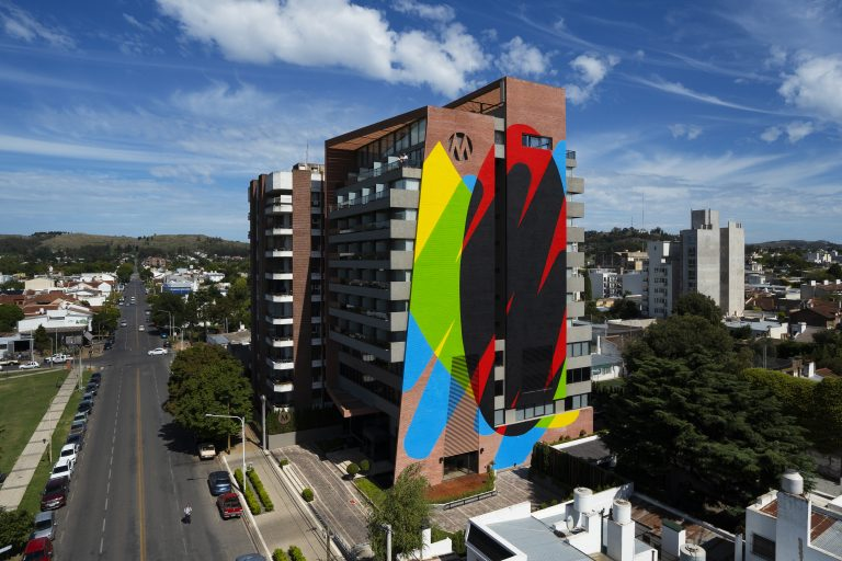 Photo of the side of a tall, brick apartment building in a mid-sized city. On the side of the building is painted a colourful mural, broad strokes of yellow, blue, green, red and black