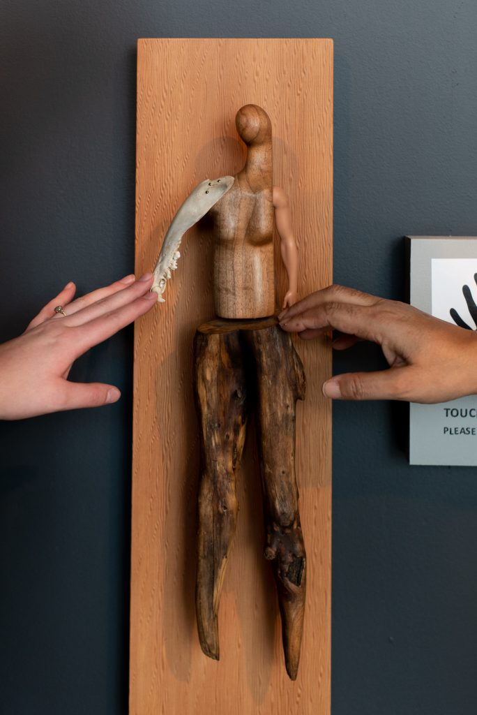 """Two hands outside the frame reaching to touch a sculpture by Persimmon Blackbridge. The piece is titled """"Soft Touch"""", and is a handcrafted figure made of wood, bone and plastic to resemble a person constructed from found objects. It is mounted on a wood panel."""