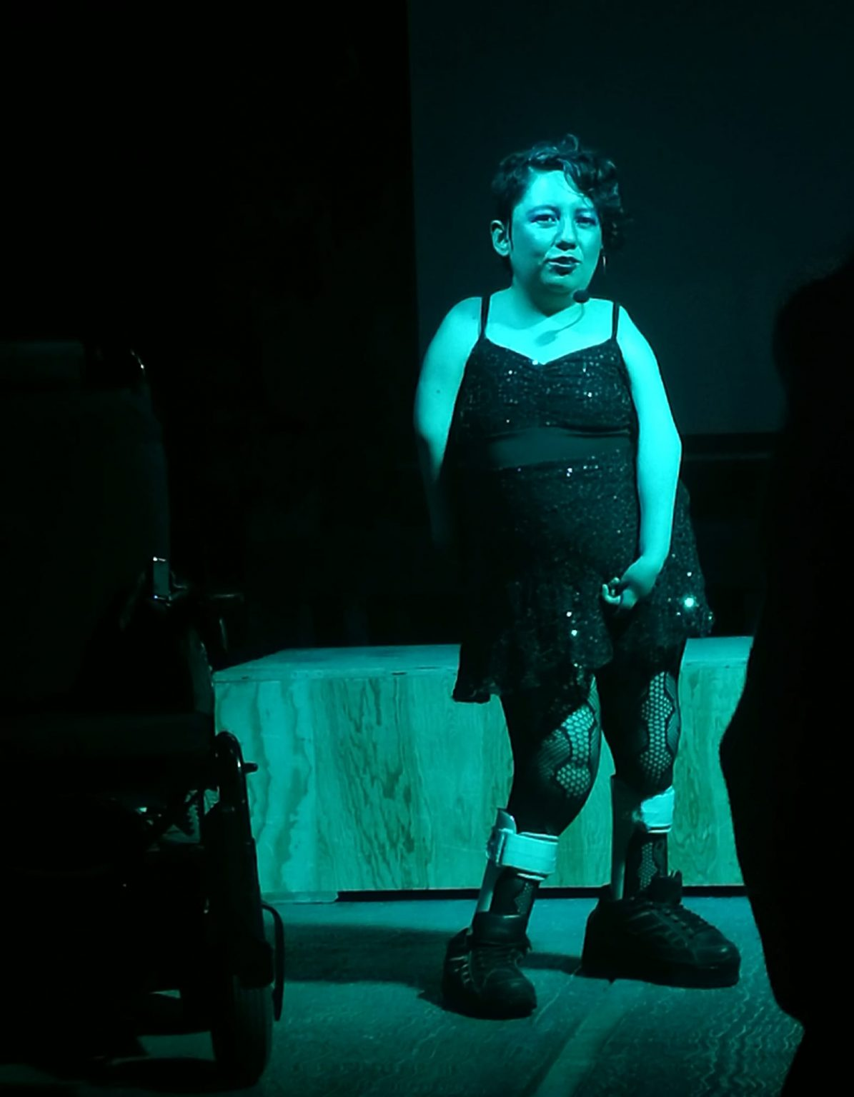 Artist Bubulina stands on a blue lit stage in front of a wooden box. They are wearing a sparkly black spaghetti strap dress with black fishnet tights, grey leg braces and black sneakers. Bubulina's short curly hair is combed over to the right and a small black microphone is looped around their right ear.