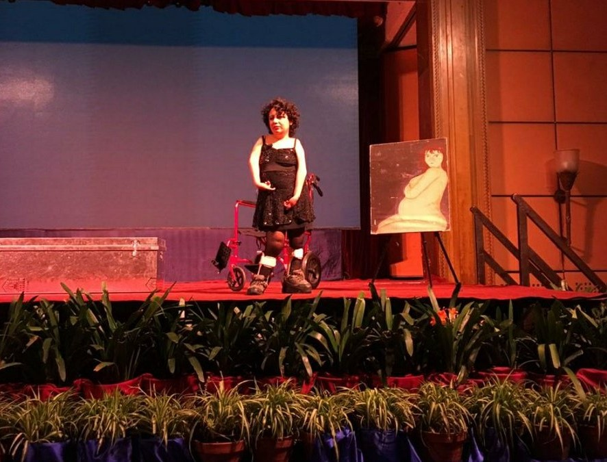 Artist Bubulina stands in the centre of a stage performing Tentáculos, the light in the room is warm and red. Behind them is their walker, next to a painting of a figure sitting tenderly holding their body. In front of the stage are two rows of green, spike-leafed plants.