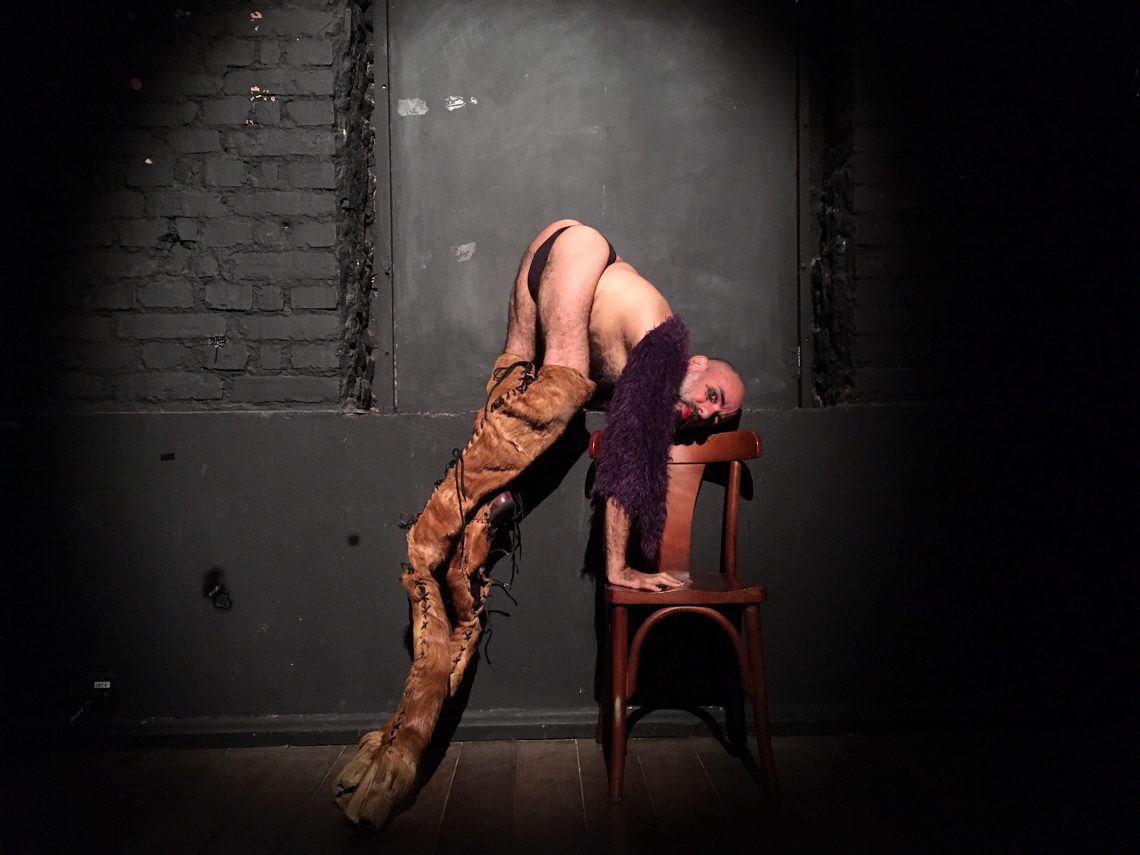 Edu O., lifting himself above a cedar chair. His arms are placed on the seat of the chair raising his body above it. He is looking directly into the camera, wearing a purple fuzzy shawl, black underwear, and long laced boots that resemble a horse's leg and hoof. In the background is a black painted wall with black painted bricks. the dark brown wooden floors.