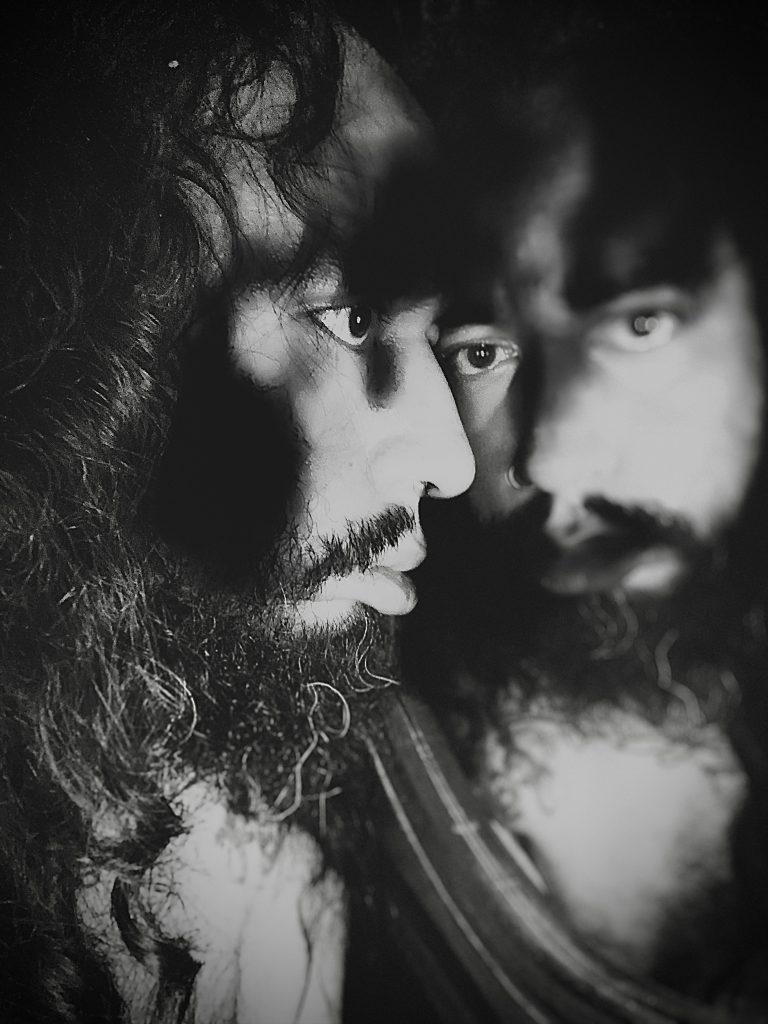 A black and white, close-up photo of artist Victor H. looking at themselves in a mirror.